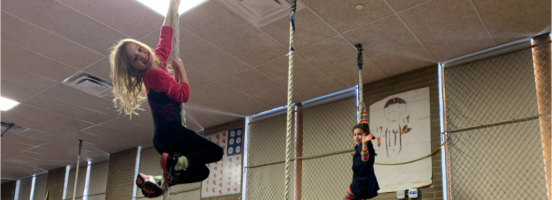 2 students hanging on ropes in the gym